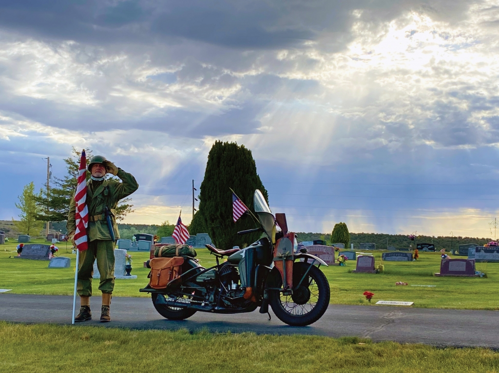 David Bieber stands at attention in the Blanding Cemetery to honor veterans on July 4. Bieber is outfitted in a World War II uniform and gear; the motorcycle is a meticulously restored Harley Davidson DWA 45 Solo. Toniee Lewis photo
